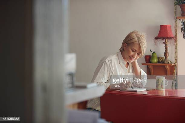 mature woman writing in journal - dagboek stockfoto's en -beelden