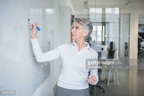 Mature woman writing on whiteboard with marker pen