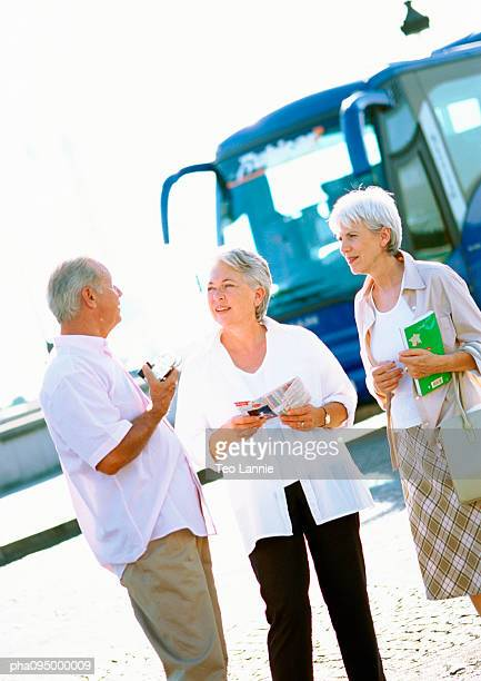 Mature women and man talking in front of a bus