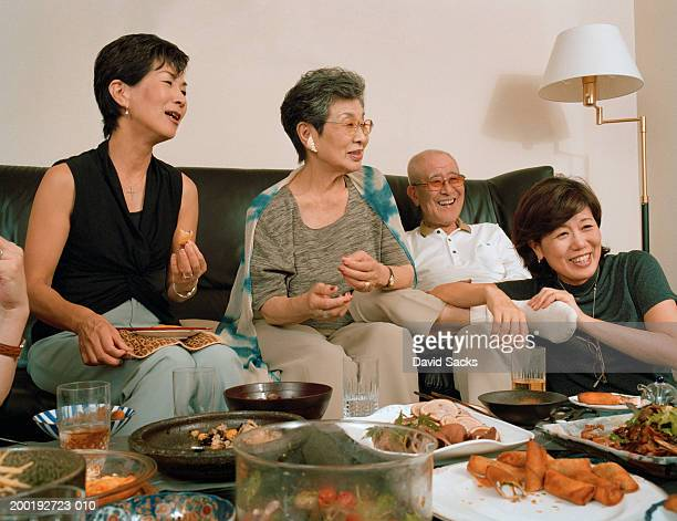 Mature women and senior man in living room with food