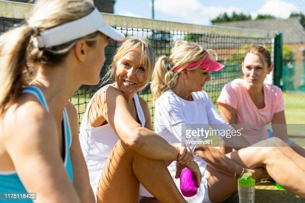 mature women at tennis club sitting on court taking a break from playing - tennis stock pictures, royalty-free photos & images