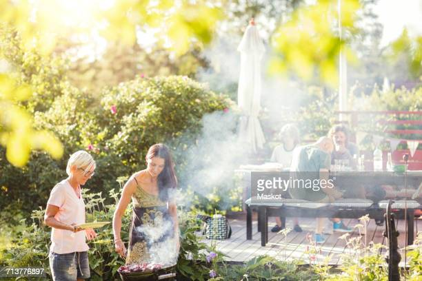 Mature women barbecuing in back yard on sunny day