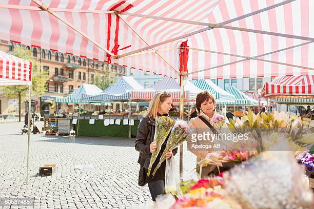 Mature women buying flowers at market stall in town square
