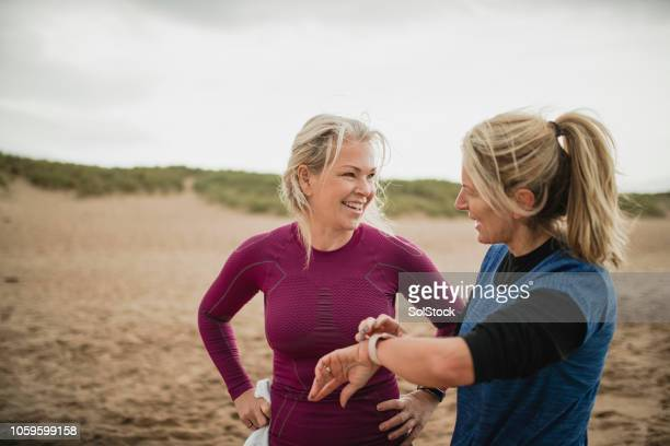 mature women checking fitness tracker - fitness tracker stock pictures, royalty-free photos & images