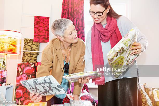 mature women comparing bedlinnen in shop. - older women in short skirts stock pictures, royalty-free photos & images