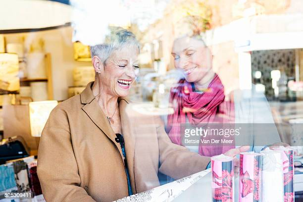 Mature women comparing wall papers in shop.