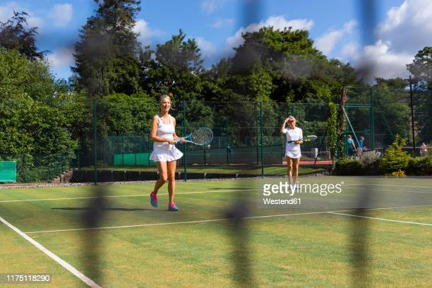 mature women during a tennis match on grass court - doubles stock pictures, royalty-free photos & images