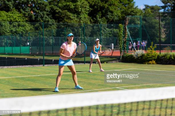 mature women during a tennis match on grass court - tennis stock pictures, royalty-free photos & images