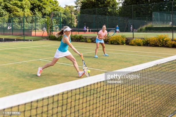 mature women during a tennis match on grass court - doppio foto e immagini stock