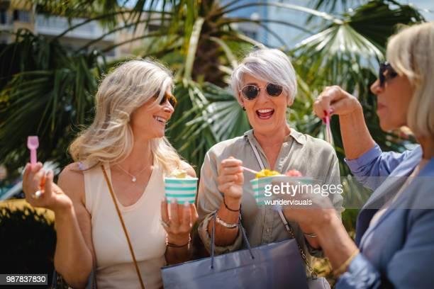 reife frauen, die eis während des einkaufs in der stadt essen - eis essen stock-fotos und bilder