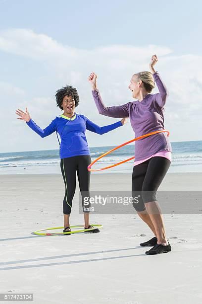 Mature women exercising on beach wth hoola hoops