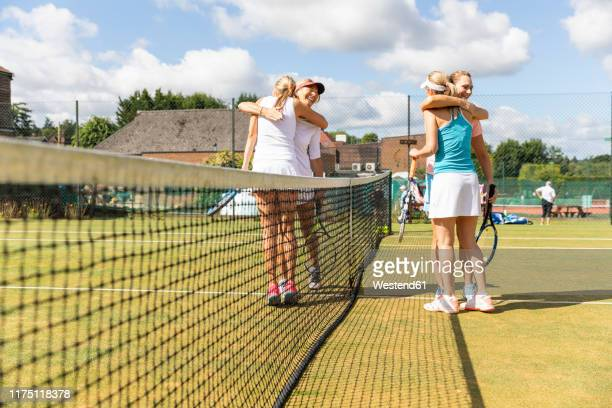 mature women finishing tennis match on grass court hugging - recreational pursuit stock pictures, royalty-free photos & images