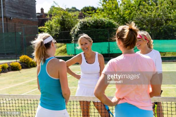 mature women finishing tennis match on grass court - doubles stock pictures, royalty-free photos & images
