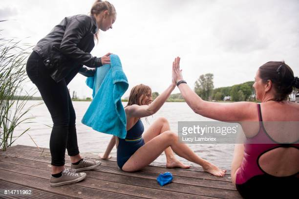 Mature women high-fiving after swimming in open water