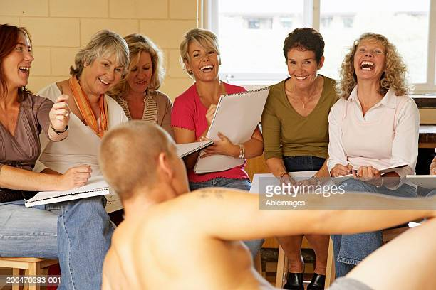 Mature women in life drawing class, smiling and laughing at male model
