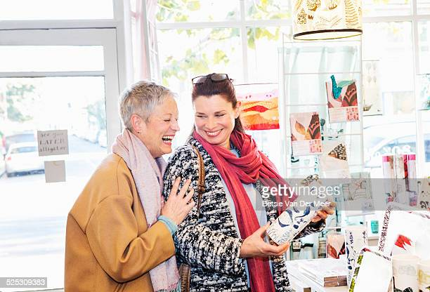 mature women laughing, looking at vase in shop. - 50 59 years stock pictures, royalty-free photos & images