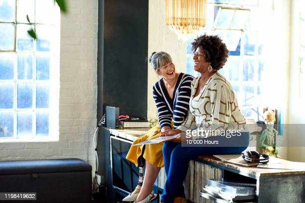 mature women laughing together in stylish loft apartment - happiness stock pictures, royalty-free photos & images