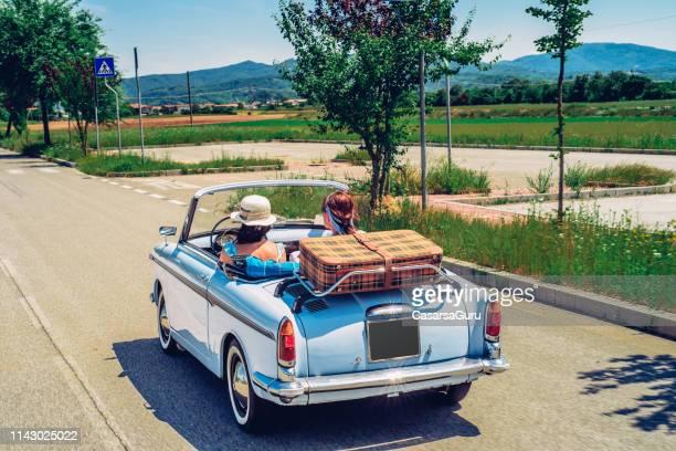 femmes d'âge mûr sur un road trip avec décapotable à l'ancienne - partir photos et images de collection