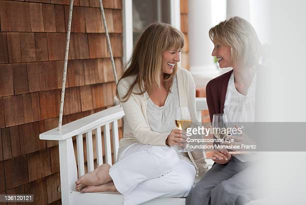 Mature women on porch swing, drinking wine