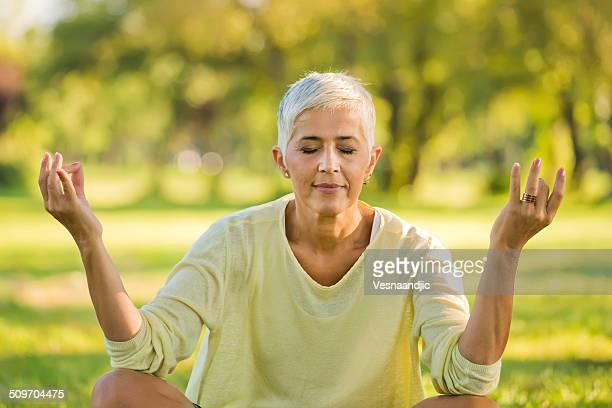 Mature women practising yoga in the meadow