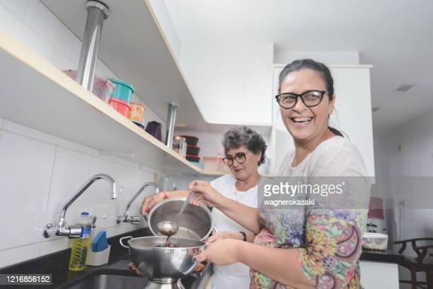 mulheres maduras preparando comida em casa (feijoada, ensopado típico de feijão preto brasileiro) - mulheres de idade mediana - fotografias e filmes do acervo