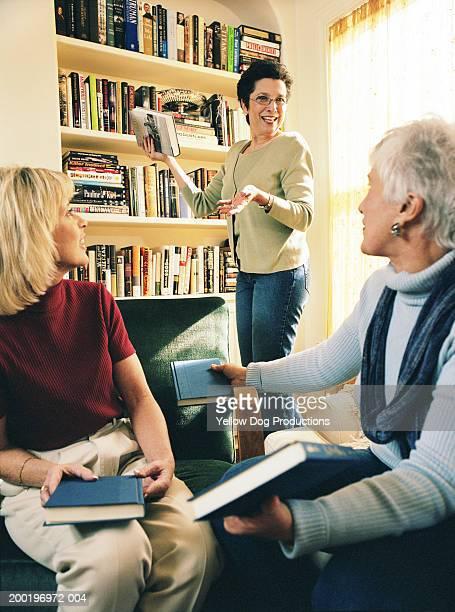 Mature women talking in living room, holding books