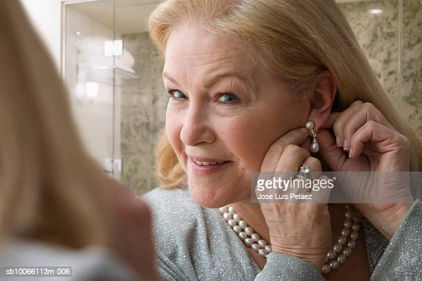 mature women wearing earring, smiling, close-up - earring stock pictures, royalty-free photos & images