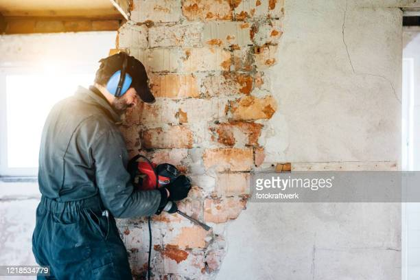 mature worker demolishing wall with drill at house - restoring stock pictures, royalty-free photos & images