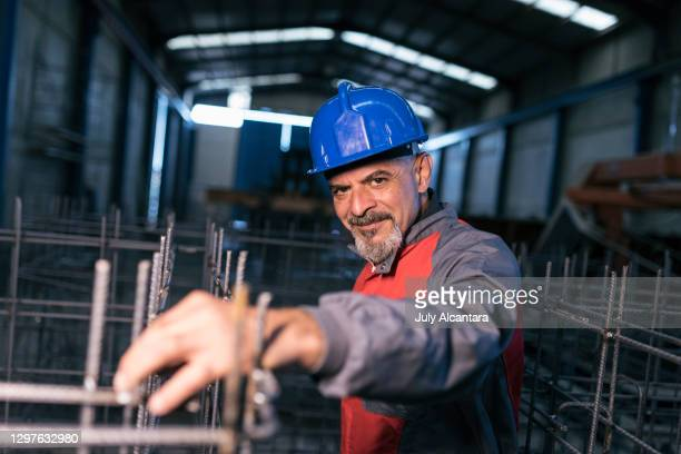 mature worker with 60 years checks the structures of rebar and looks at camera in a factory of concrete structures and buildings - 55 59 years stock pictures, royalty-free photos & images