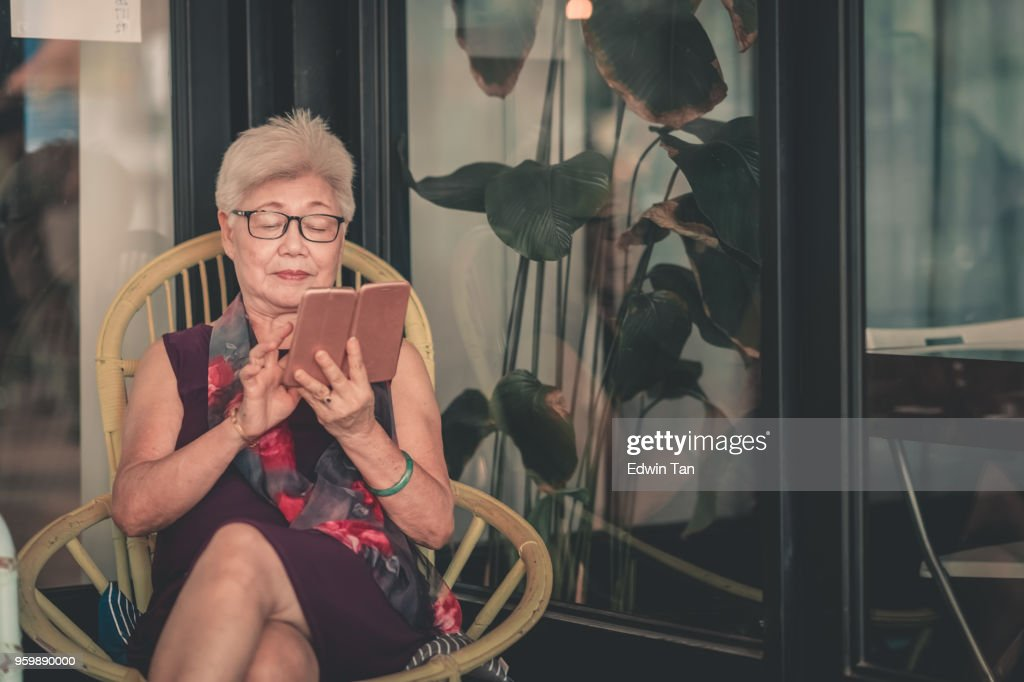 matured asian chinese female looking on her phone : Stock Photo