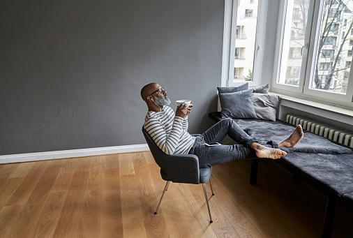 Matureman with earphones sitting at window, drinking coffee - gettyimageskorea