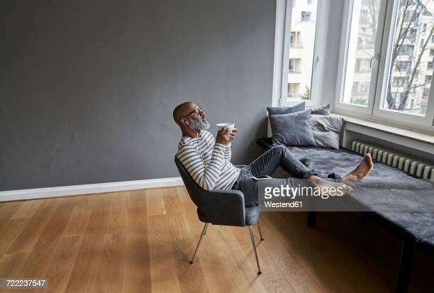 Matureman with earphones sitting at window, drinking coffee