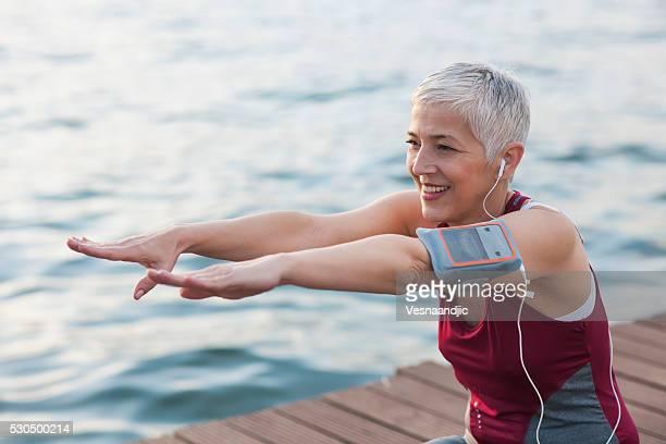 マチュア-年配の女性ジョギング海のそばで