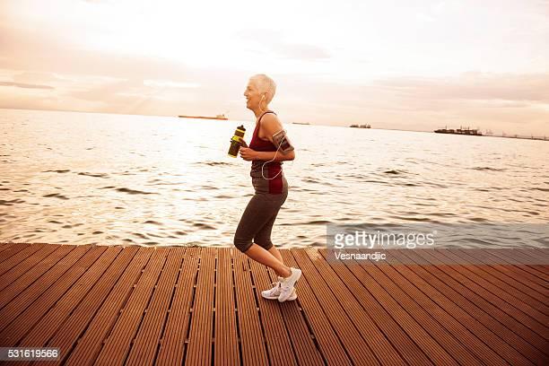 Mature-senior woman jogging beside the sea