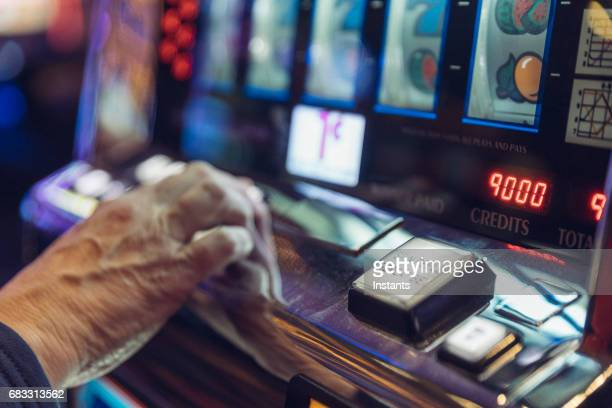 A mature/senior woman, sitting in front of a slot machine, is gambling in a Las Vegas casino.