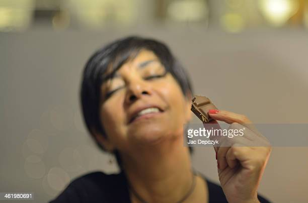 maturewoman enjoying eating chocolate - depczyk stock pictures, royalty-free photos & images