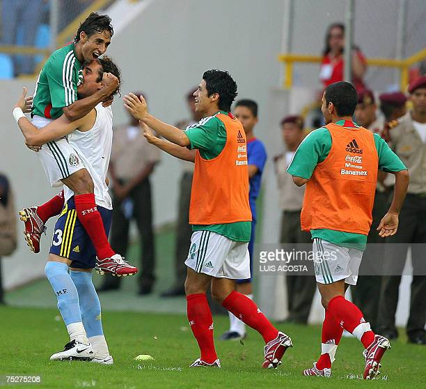 Mexico's Fernando Arce is lifted up by goalkeeper Guillermo Ochoa after scoring the fourth goal of his team against Paraguay during their Copa...
