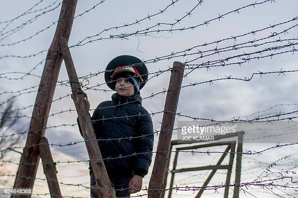 TOPSHOT Matus a sevenyearold Slovak boy wears a Soviet military hat as he stands by remains of the border fences from the former 'Iron curtain'...