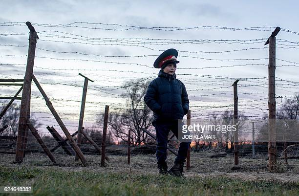 Matus a sevenyearold Slovak boy wears a Soviet military hat as he stands by remains of the border fences from the former 'Iron curtain' between...