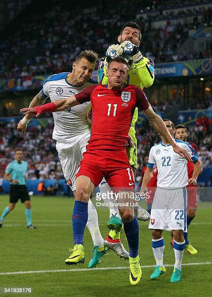 Matus Kozacik of Slovakia and teammate Jan Durica jump for a header with Jamie Vardy of England during the UEFA Euro 2016 Group B match between...