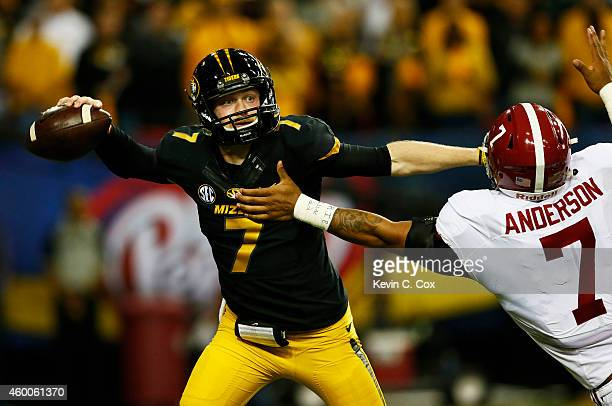 Maty Mauk of the Missouri Tigers passes under pressure from Ryan Anderson of the Alabama Crimson Tide in the first quarter of the SEC Championship...