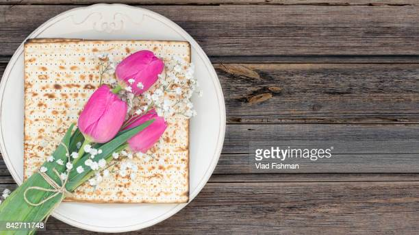 matzah or matza on a white plate and a tulip flowers on a vintage wood background with copy space. - happy passover stock pictures, royalty-free photos & images