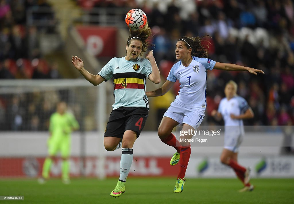 Maud Coutereels of Belgium wins a header over Fara Williams of England during the UEFA Women's European Qualifer between England and Belgium at The New York Stadium on April 8, 2016 in Rotherham, England.