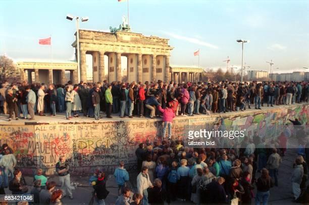 Mauerfall: Öffnung Grenze BRD/DDR: Menschen besteigen die Berliner Mauer vor dem Brandenburger Tor .