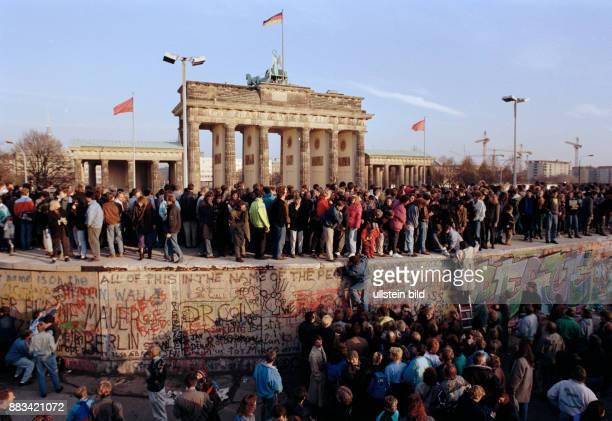 Mauerfall: Oeffnung Grenze BRD/DDR: Menschen besteigen die Berliner Mauer vor dem Brandenburger Tor , Berlin