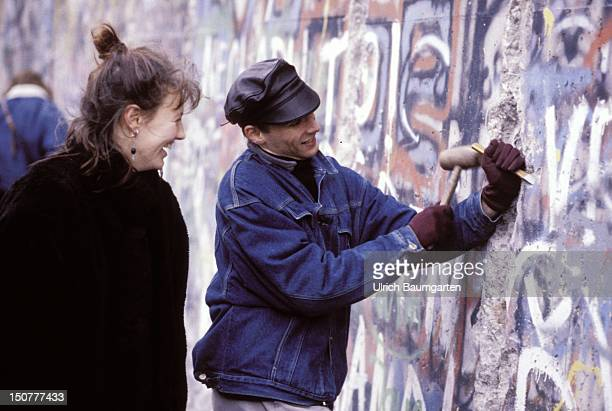 Mauerspechte Couple is knocking stones out of the Berlin wall