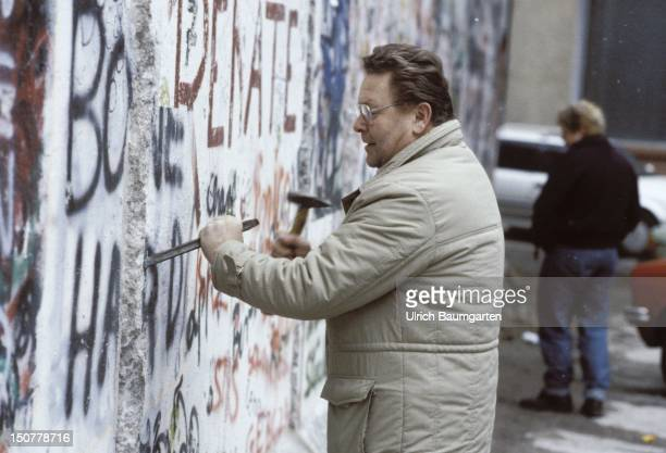 Mauerspechte Man is knocking stones out of the Berlin wall