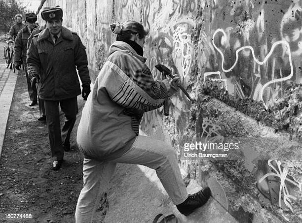 Mauerspechte woman is knocking stones out of the Berlin wall In the Background GDR border police