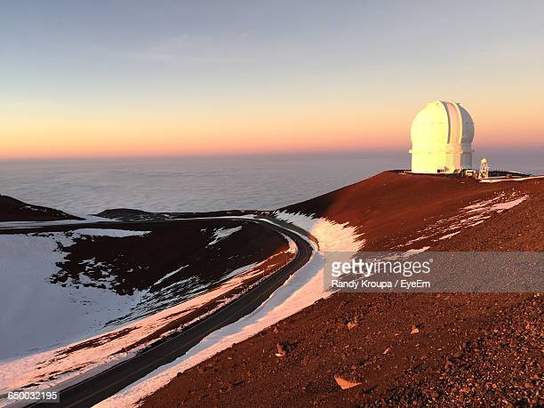 mauna kea observatory on volcanic mountain by cloudscape against sky during sunset - observatory stock pictures, royalty-free photos & images