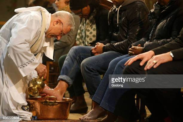 Maundy Thursday celebration in a Parisian catholic church Priest washing faithfuls' feet